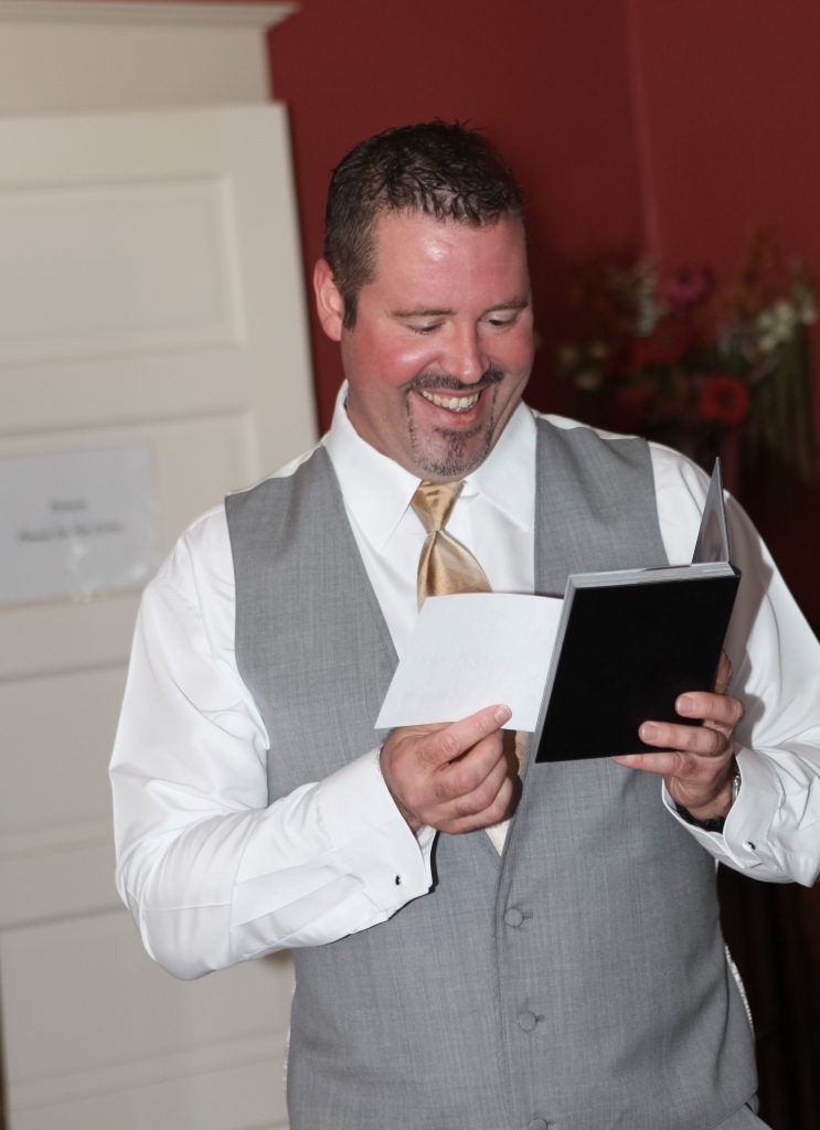 Groom's gift idea. This is a wedding image of a man receiving a boudoir photo album as his wedding gift. For more info about boudoir photography, visit byRayleigh.com