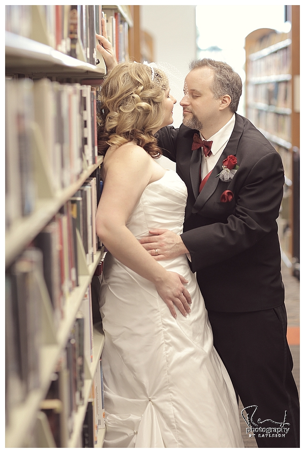 Valentine's Day Library wedding. Wedding Photography by Rayleigh. This image is of the bride and groom kissing embracing among the books. She's wearing a netted bird cage veil headband. For more info, visit byrayleigh.com