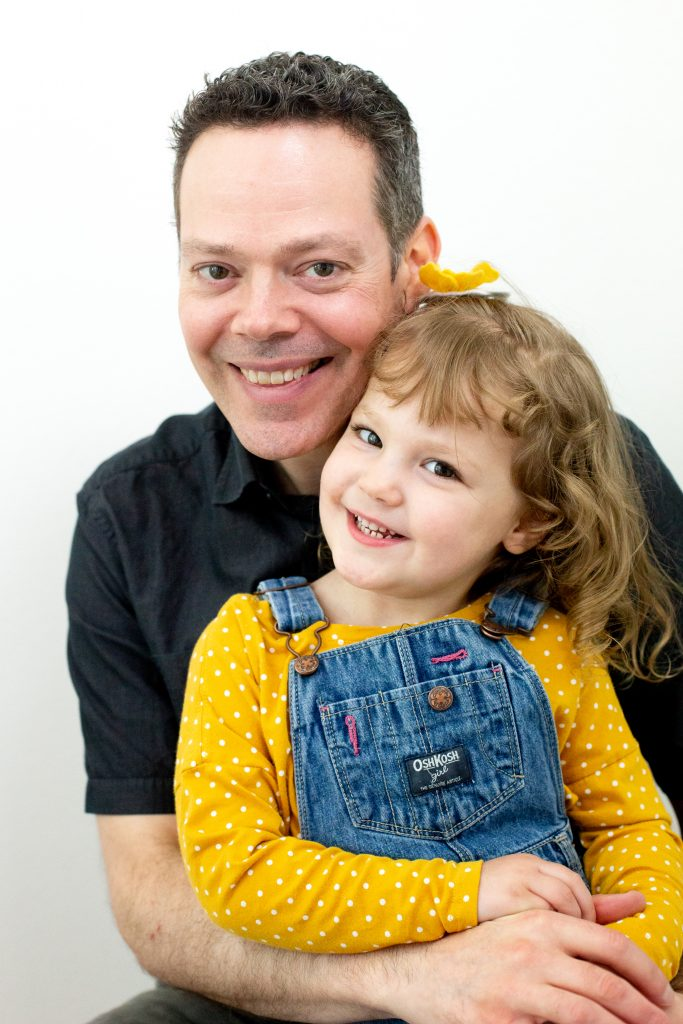 Father's Day gift ideas. This family photo was taken with natural light in a studio with a father and his daughter embracing and smiling in front of a white background. He is wearing a black polo shirt and she is wearing a yellow polka dot long sleeve t-shirt with overalls and a yellow flower in her hair. This photo was taken by Photography by Rayleigh in Portland, OR. See more at byrayleigh.com.