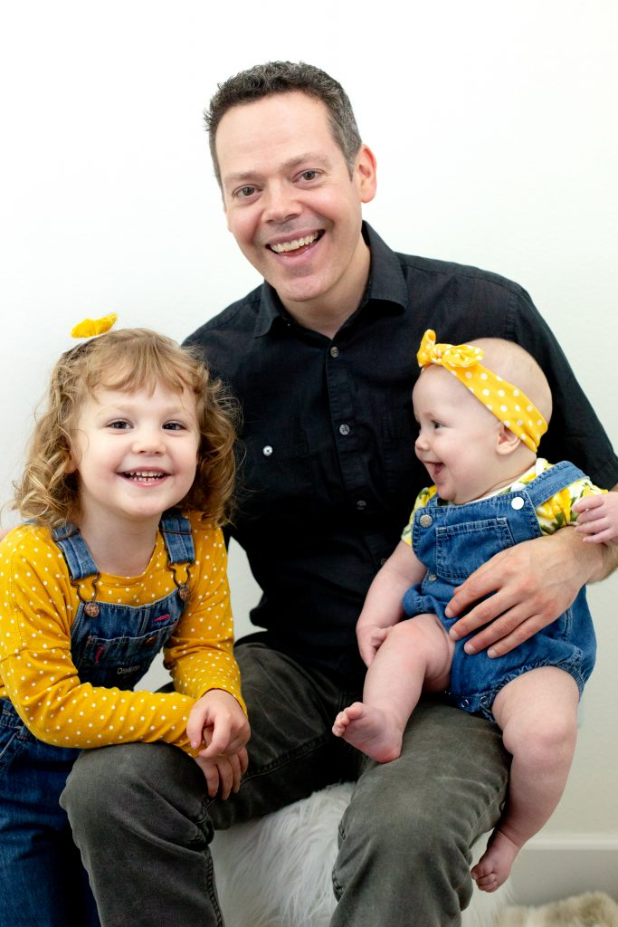 Father's Day gift ideas. This family photo was taken with natural light in a studio with a father and his daughters embracing and smiling in front of a white background. He is wearing a black polo shirt and the girls are wearing yellow polka dots with overalls and a yellow hair accessories. This photo was taken by Photography by Rayleigh in Portland, OR. See more at byrayleigh.com.