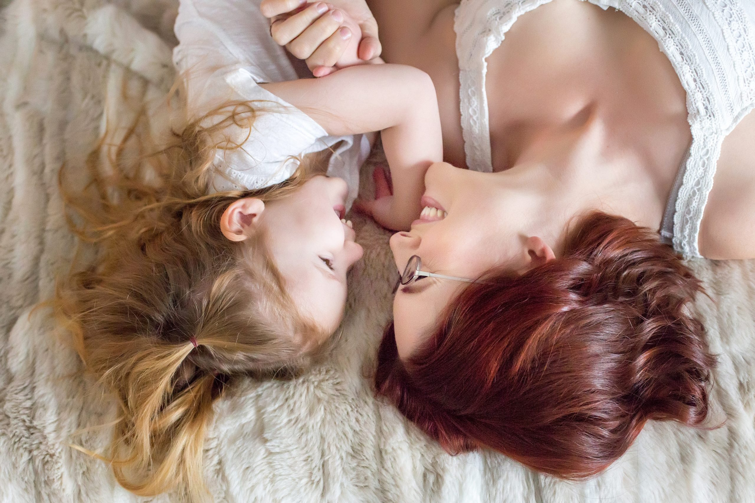 Teach your daughter what true beauty is. This mother-daughter image is of a young child, smiling at her mother while hugging. Photography by Rayleigh. For more info, please visit byRayleigh.com
