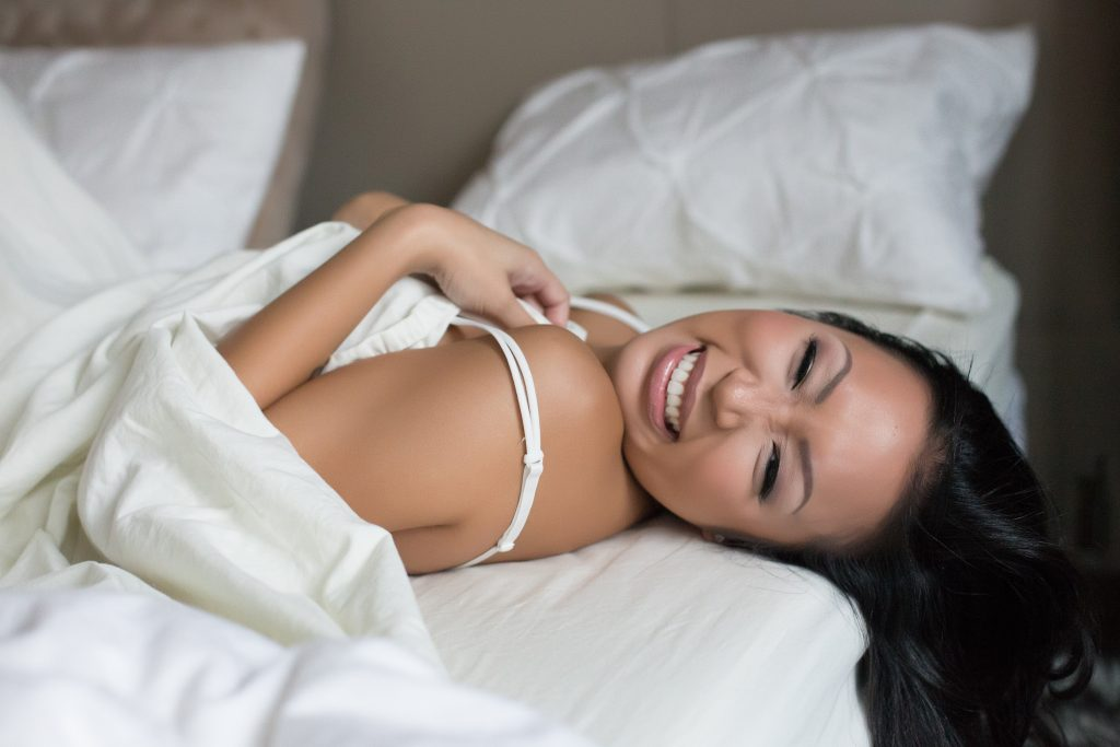 7 tips for feeling confident while being photographed. This is a modest boudoir image in a photography studio of a smiling Asian woman lying on her back on the bed, covered by white sheets. Photography by Rayleigh. For more info, please visit byRayleigh.com