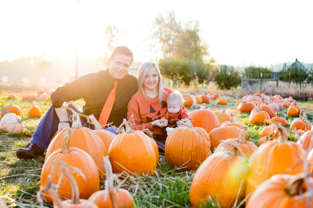 Ideas for how to dress for a Fall photo shoot. Photography by Rayleigh in Portland. This family is wearing orange and black shirts with jack-o-lantern faces while sitting in a pumpkin patch. They backlit by the setting sun. For more info, see byRayleigh.com.