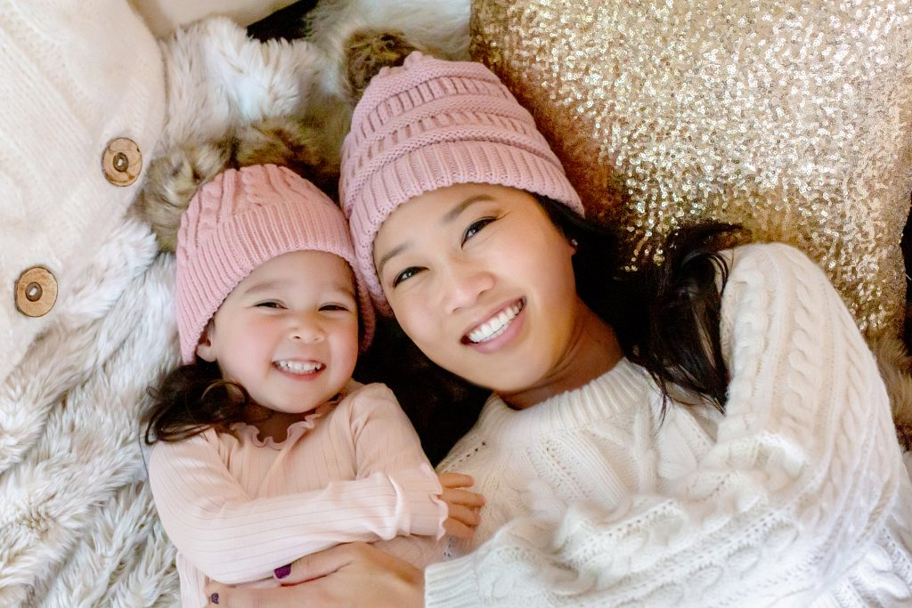 Christmas pajama sessions. This is an image of an Asian mother with her daughter, lying on the floor ans smiling. They are wearing sweaters and matching pink winter hats. Image by Photography by Rayleigh. For more info, visit byrayleigh.com