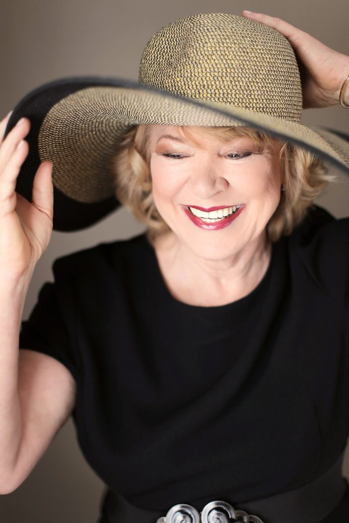 boudoir photo shoot in your 60's. This is an image of woman in her 60's, smiling and holding her hat against a brown background. Photography by Rayleigh. For more info, please visit byRayleigh.com