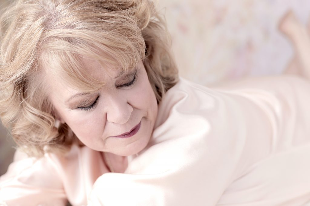 boudoir photo shoot in your 60's. This is a modest boudoir image of woman in her 60's, smiling while lying on her tummy on the bed, in front of a pink floral background. She is wearing a pink silk robe. Photography by Rayleigh. For more info, please visit byRayleigh.com
