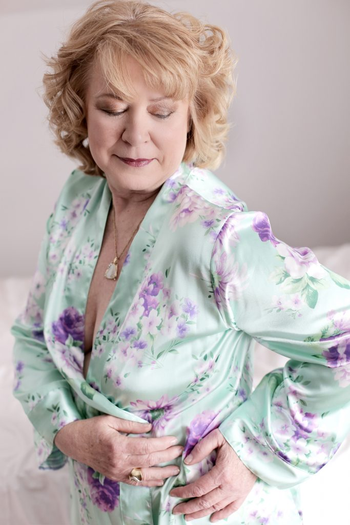 boudoir photo shoot in your 60's. This is a modest boudoir image of woman in her 60's, smiling while standing in front of a bed and a white background She is wearing a teal and purple silk floral robe. Photography by Rayleigh. For more info, please visit byRayleigh.com