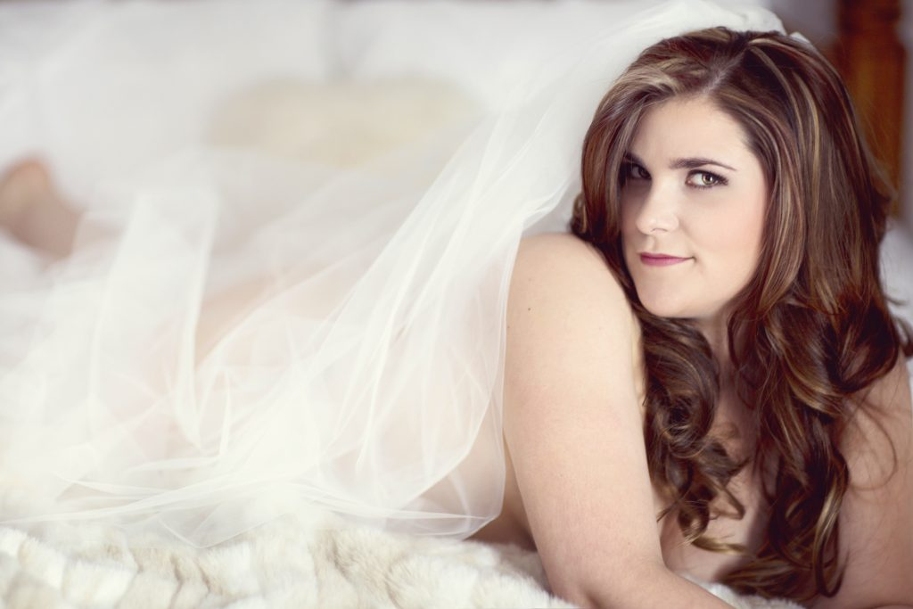 Bridal boudoir shoot. This is a boudoir pose of a woman in her wedding veil, lying on her tummy on the bed. Photography by Rayleigh. For more info, please visit byRayleigh.com