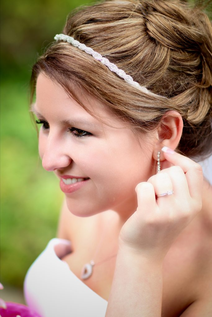 Brownsville, OR wedding photographer. This candid outdoor wedding portrait is of a smiling bride , fixing her earring. Photography by Rayleigh. For more info, please visit byRayleigh.com
