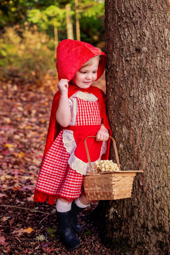 Ideas for how to dress for a Fall photo shoot. Photography. This young girl is wearing a Little Red Riding Hood costume outside next to a tree with Fall leave on the ground. For more info, see byRayleigh.com.