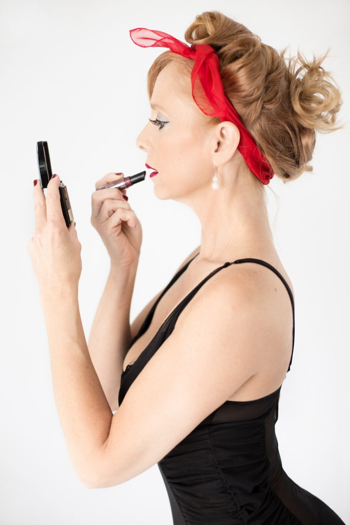 What to wear for your retro pin up photography session. This image is of a woman standing against a white wall, wearing black lingerie. she is applying lipstick. Photography by Rayleigh. For more info, please visit byrayleigh.com