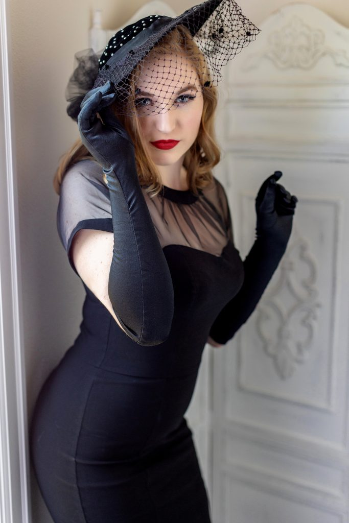What to wear for your retro pin up photography session in Portland. This is an 50's inspired image of a woman wearing a black pencil wiggle dress, vintage bird cage hat, and long black gloves. Pin Up photography by Rayleigh. See more at byrayleigh.com