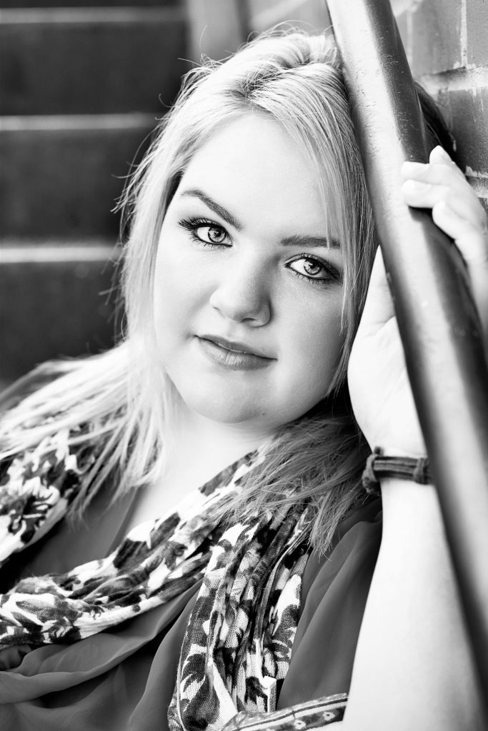 Outdoor senior pictures. This is a black and white image of a plus size teen girl sitting on the stairs and leaning against a brick wall. Photography by Rayleigh. For more info, please visit byRayleigh.com